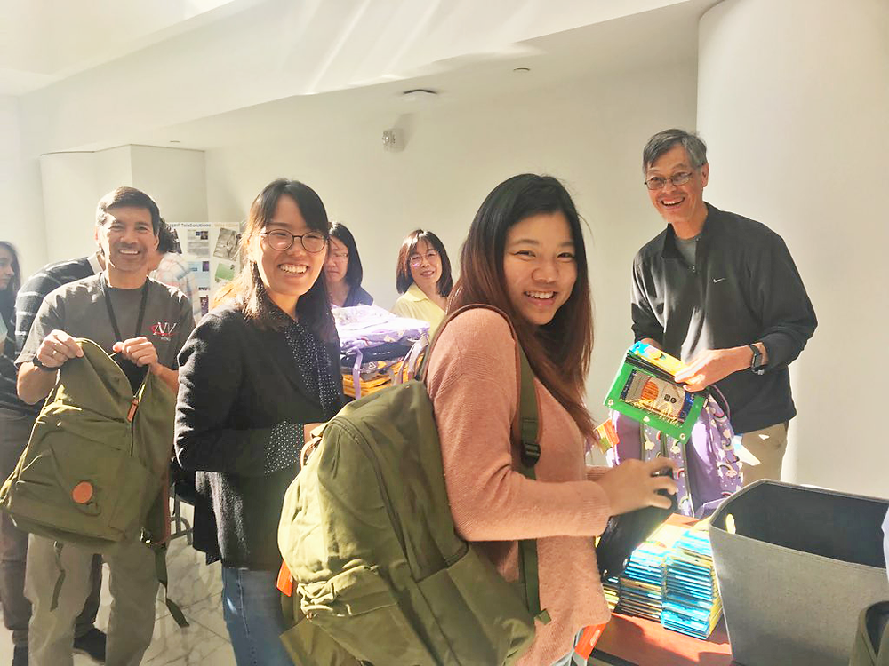 AT&T volunteers happily packing supplies into backpacks for Mount Diablo Unified School District