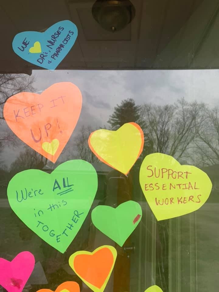 """signs on a door which state """"we love nurses, doctors and pharmacists"""", """"keep it up"""", and """"we support essential workers"""""""