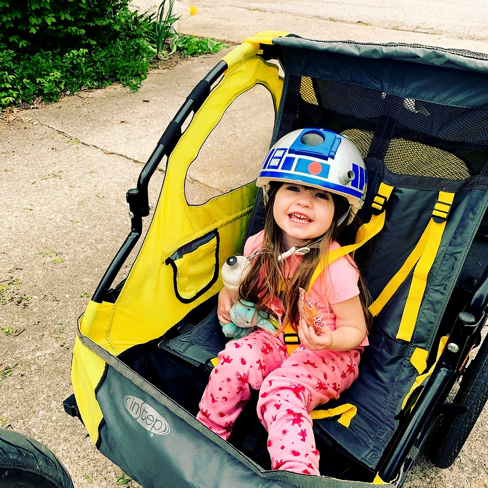 Toddler in a bike trailer with an R2D2 helmet