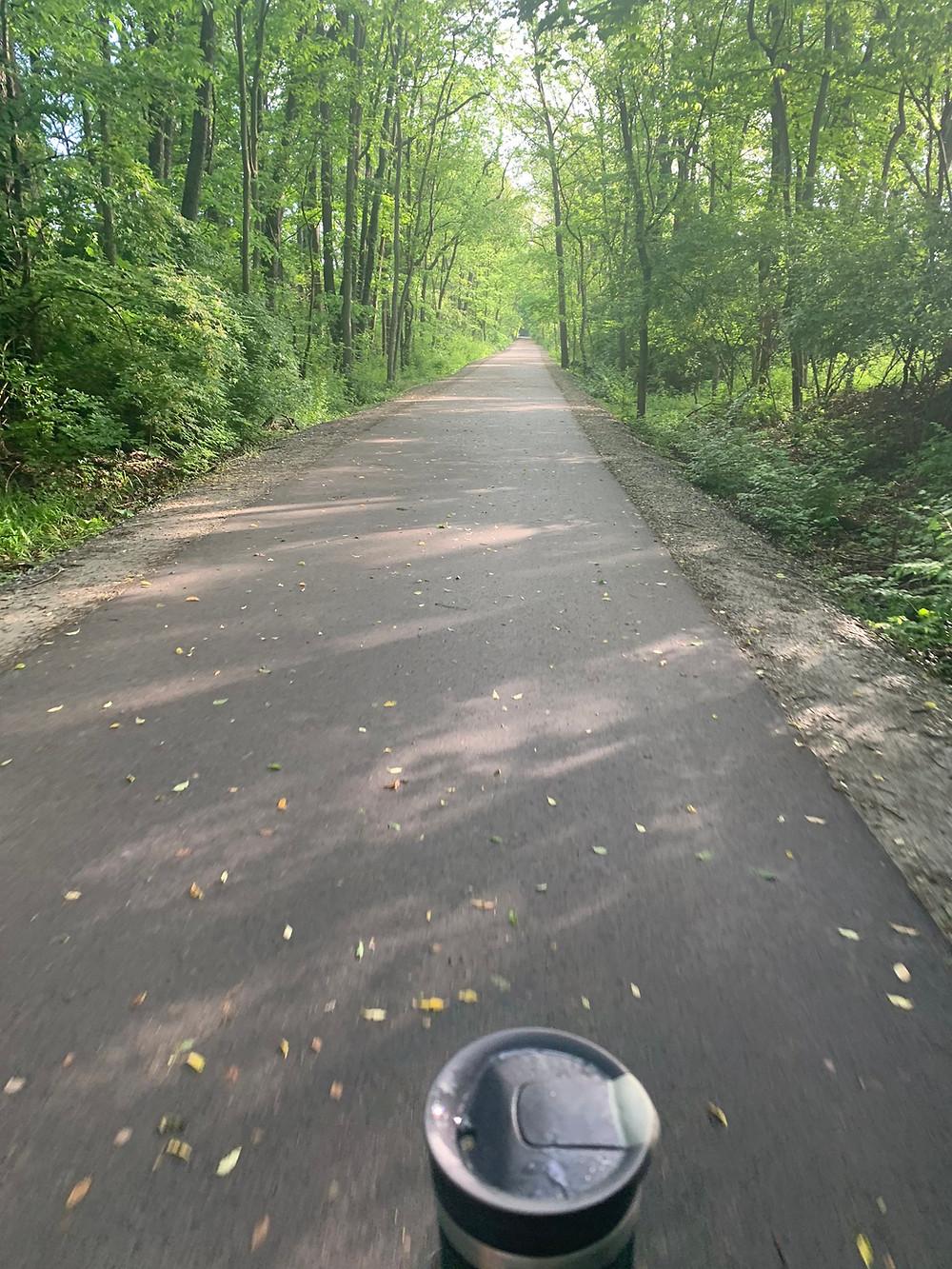 a coffee cup on a bike on a desolate paved trail