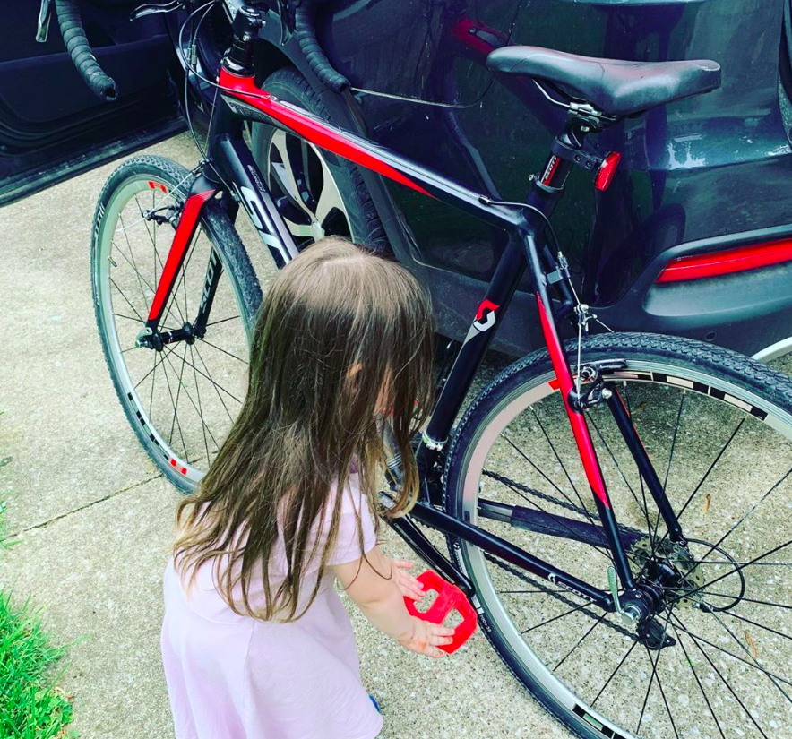 toddler playing with pedals of a road bike