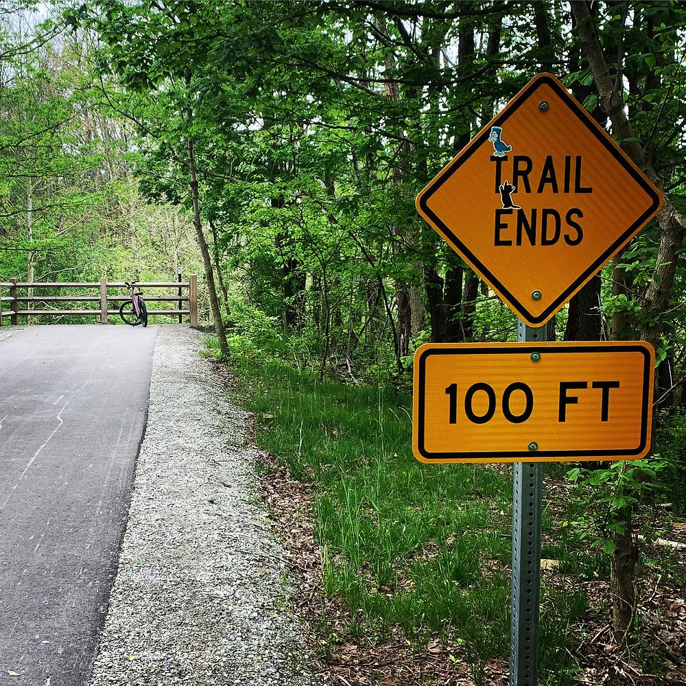purple e-bike and a trail ends sign on a paved trail