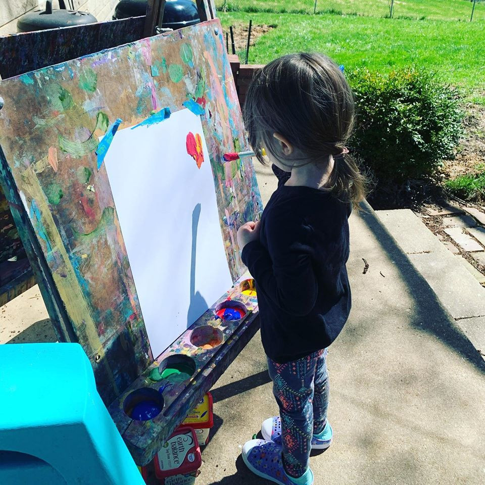 girl stands at an easel painting