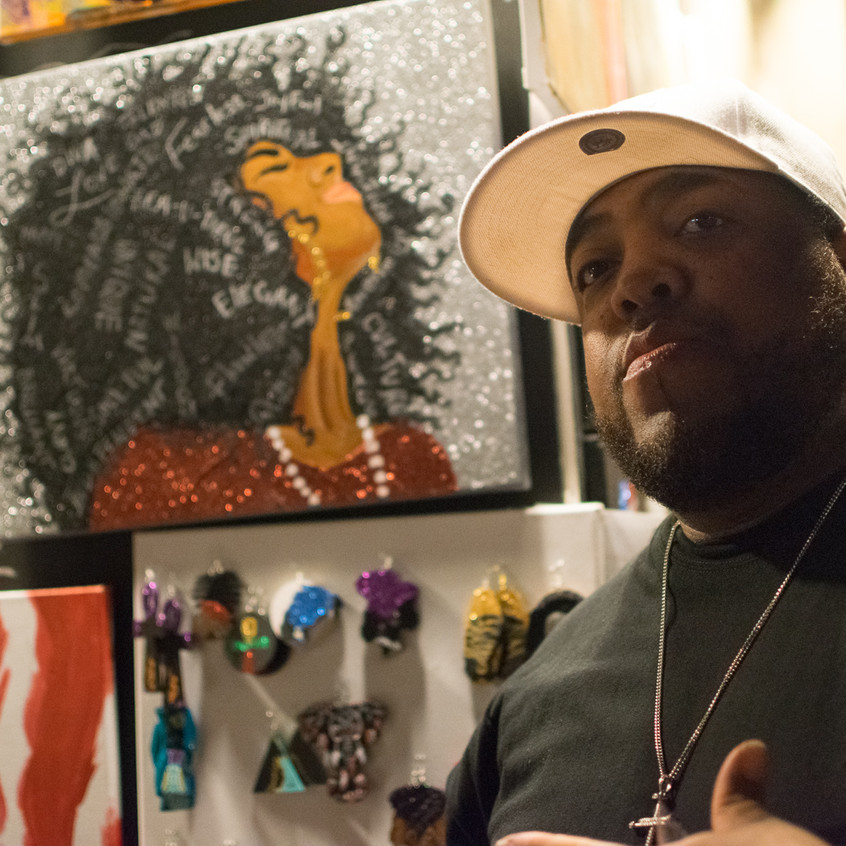 @jatsodezigns posing with his handpainted artwork.
