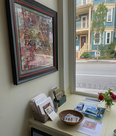 on the wall, Grey Held's framed rain poem, and various small works and cards by Regarding Water artists