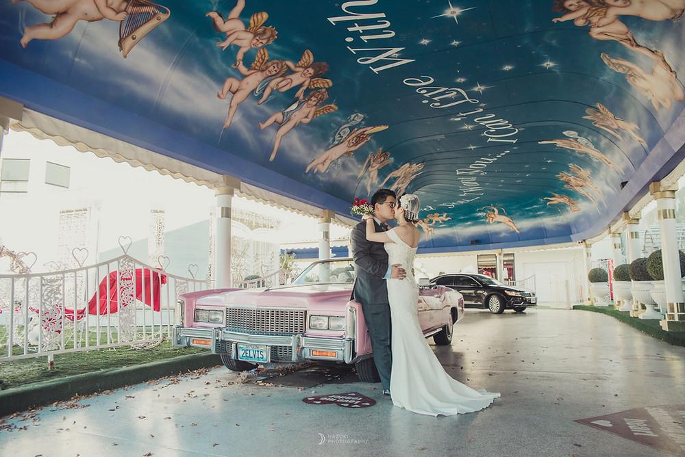 ドライブスルー挙式会場のピンクのキャデラックの前で誓いのキスをする新郎新婦