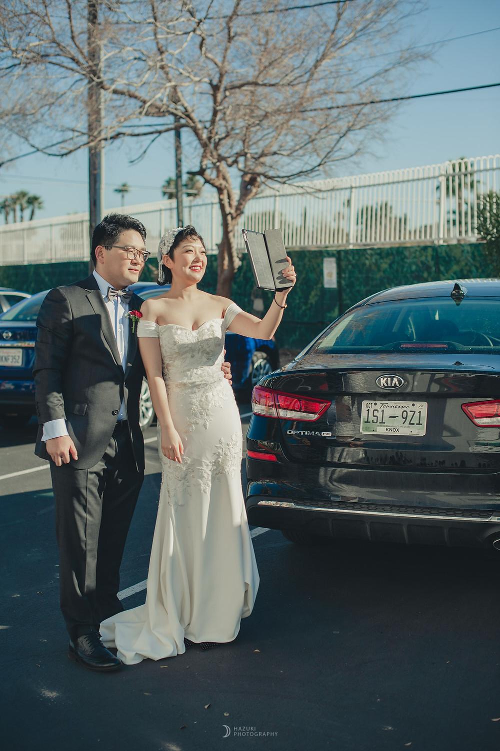 ドライブスルー挙式会場の外でタブレット端末の家族と電話する新郎新婦