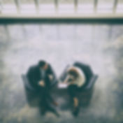 Two people sitting in the office armchairs and discussing