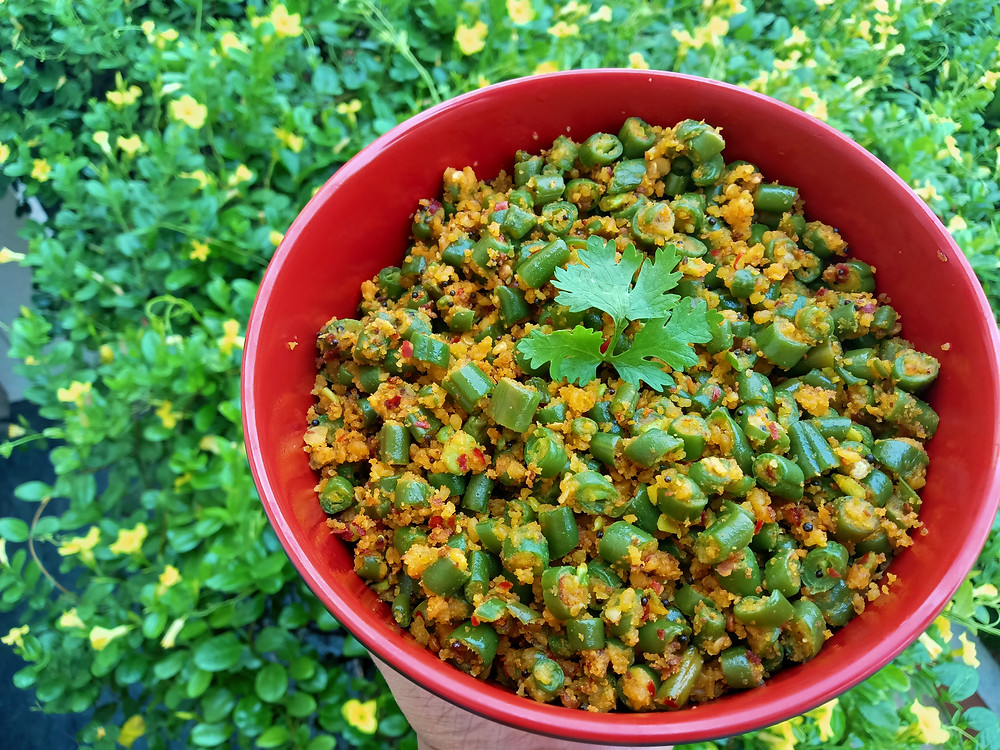 Beans and lentlil usili served in red bowl and garnished with coriander