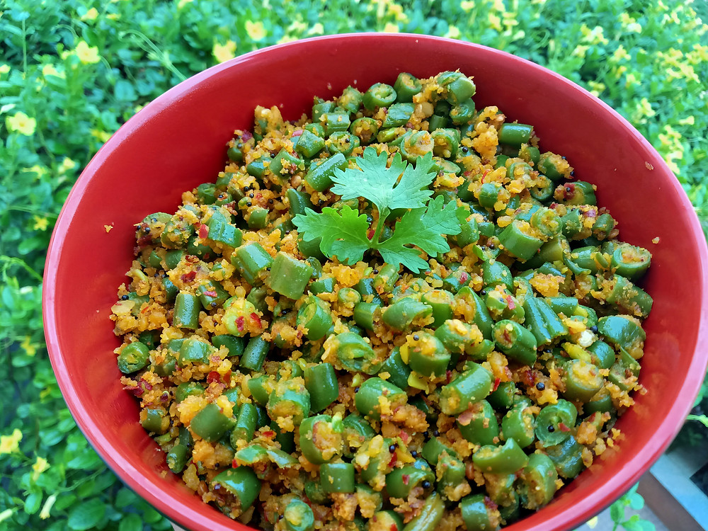 Beans usili served in red bowl and garnished with coriander.