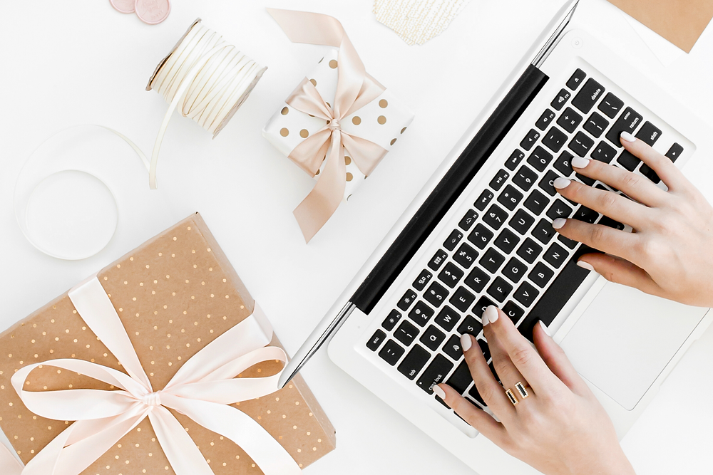 Woman typing on laptop with Christmas gifts on desk