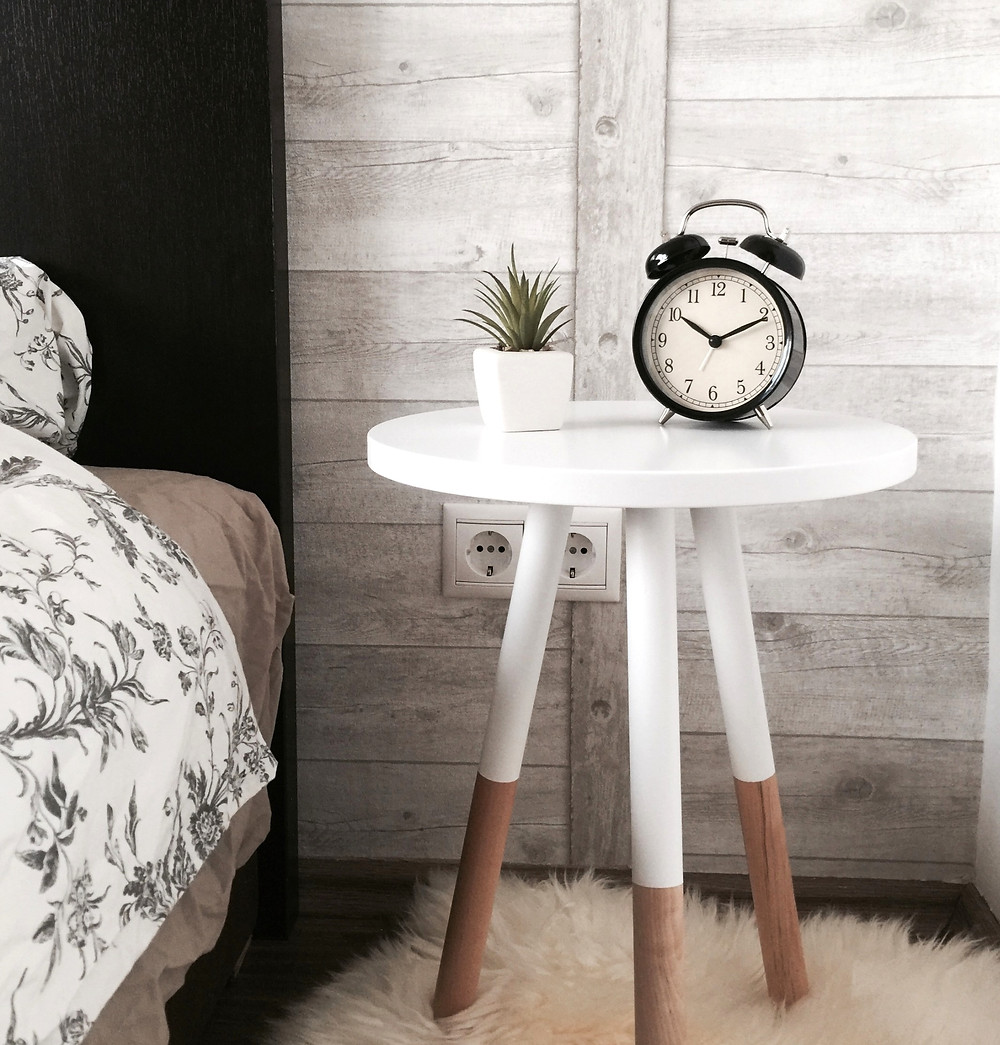 Bedside table with a black alarm clock and plant