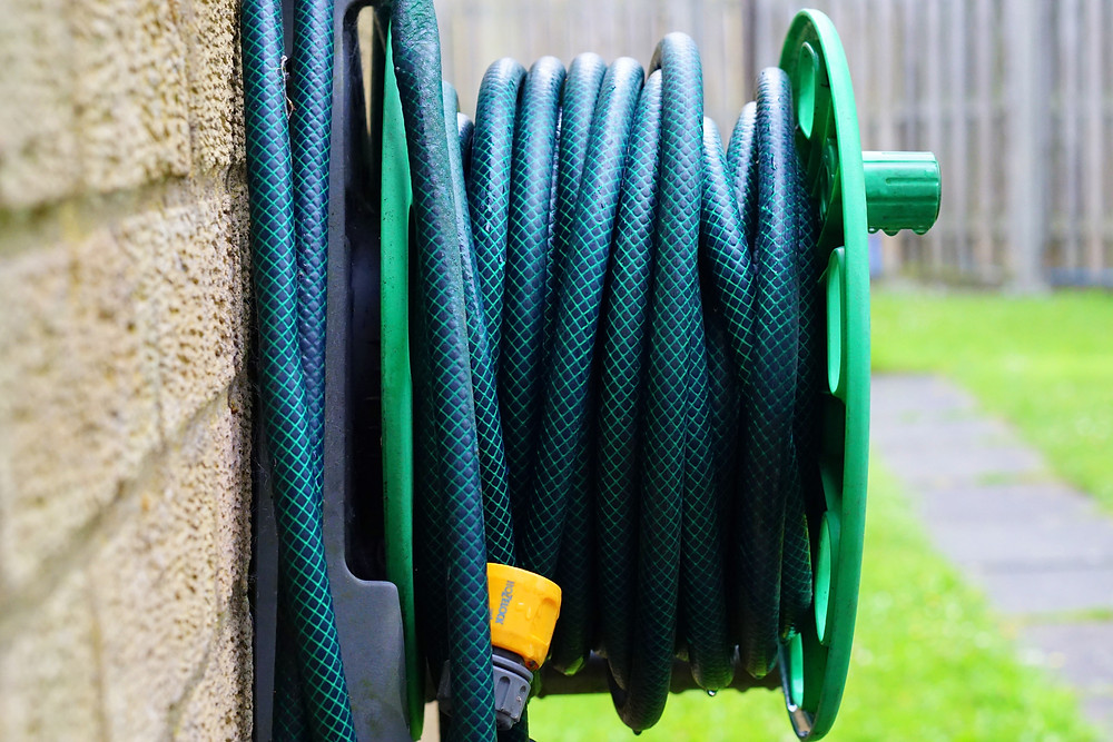 Rolled up green hose on the side of a house