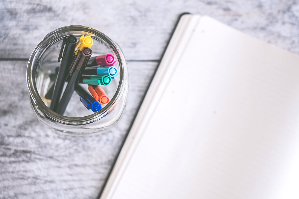 Open blank notebook with jar of colored pens