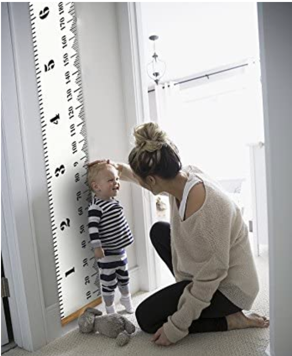 Mom measuring child's growth on large wall ruler