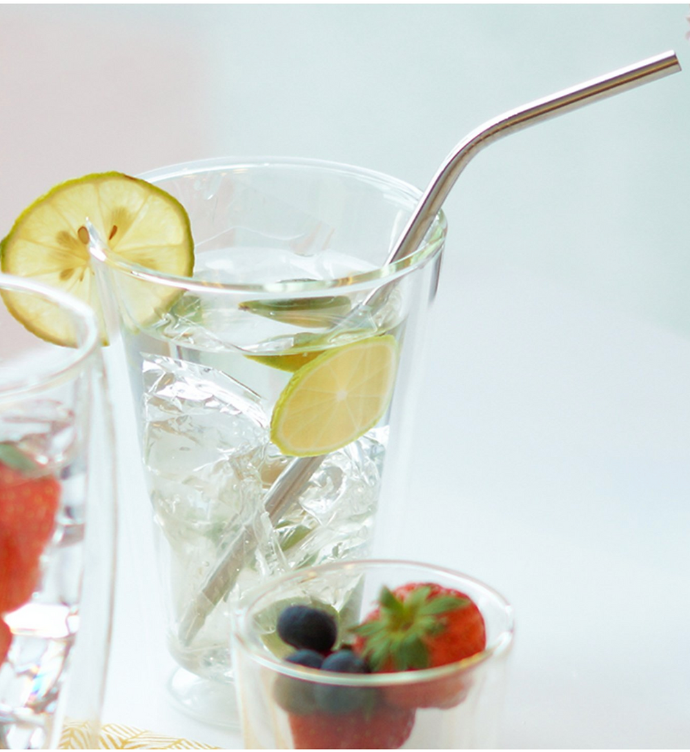 Glass with fruit and metal stainless steel straw