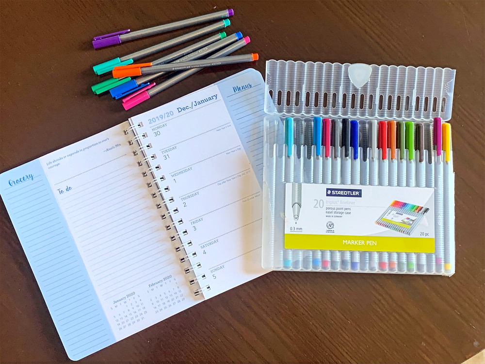 Blank open calendar planner with box of colored pens