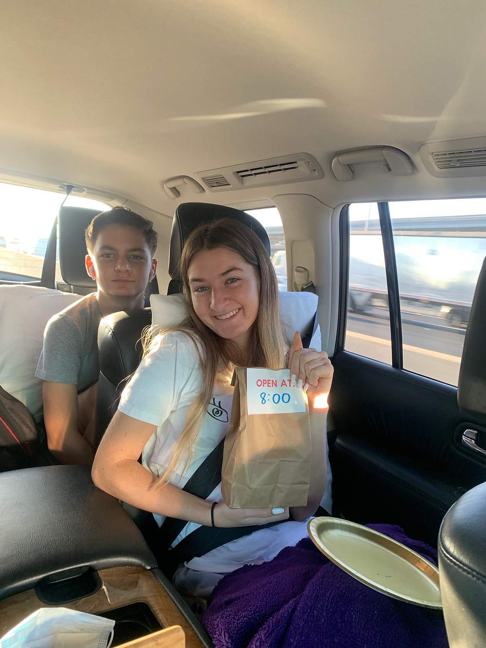 Kids in car for road trip with travel goodie bag