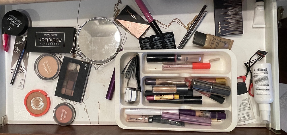 Messy drawer full of makeup supplies and cosmetics
