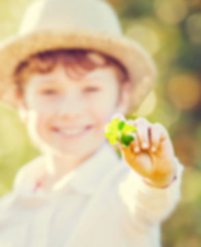 Happy boy in hat holds lucky four leaf c