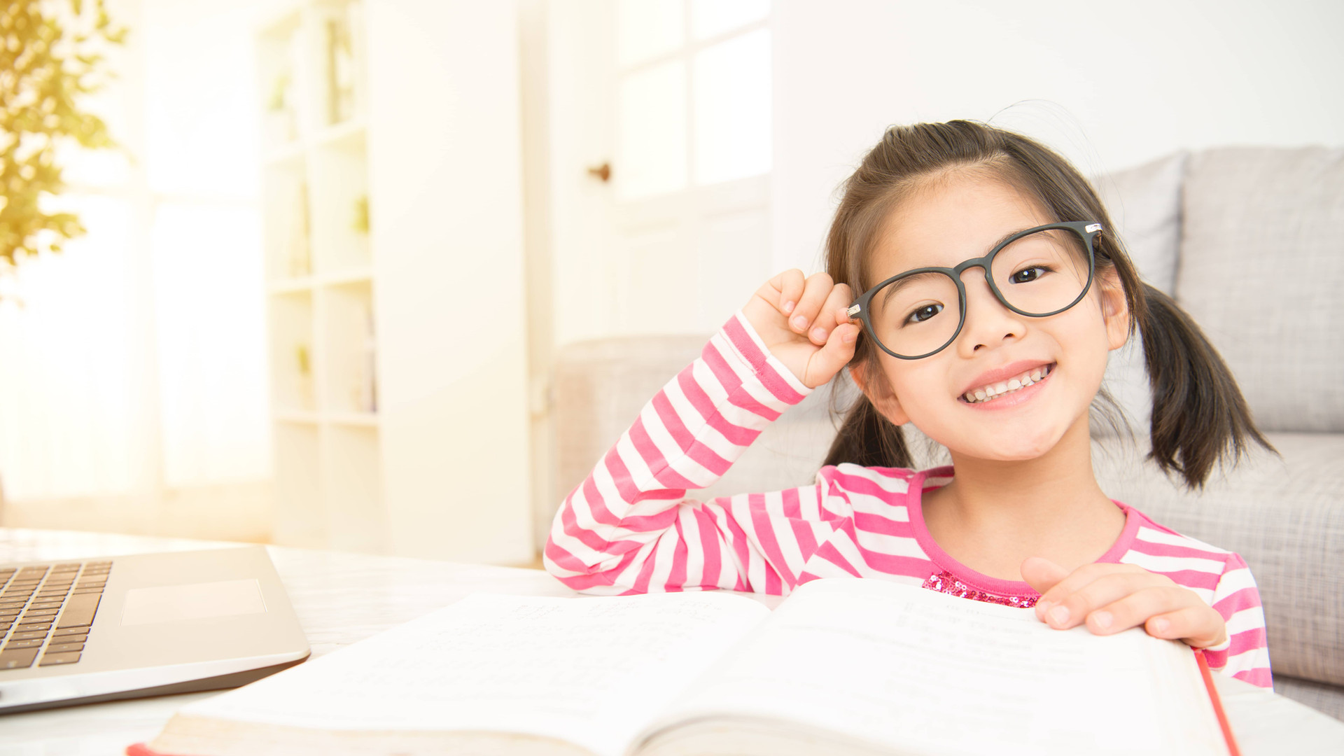 little girl reading with glasses