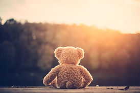 A lone teddy bear staring into lonliness.