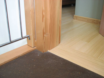 Bamboo flooring installed over plywood subfloor adjacent to earthen floor. Barefoot Radiant Heating.