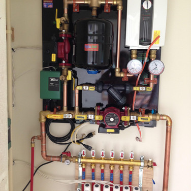 An electric boiler on a pre-made panel powers this multi-zone radiant floor heating system. Barefoot Radiant Heating.