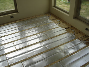 Plywood sleepers with tubing an aluminum heat distribution plates.  Barefoot Radiant Heating.