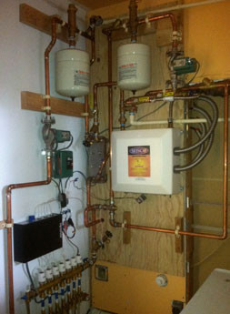 Electric tankless water heater used to heat the water for the radiant floor heating system as well as to make domestic hot water. Barefoot Radiant Heating.