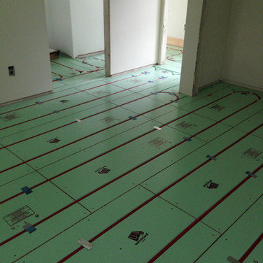 Tubing installed in Warmboard R panels on top of sub-flooring in new home. Barefoot Radiant Heating.