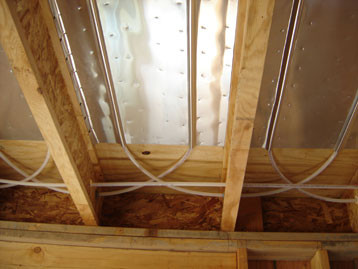 Tubing stapled to the bottom of a plywood subfloor with aluminum heat distribution plates.  Barefoot Radiant Heating.