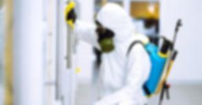 person-wearing-hazmat-suit-disinfecting-