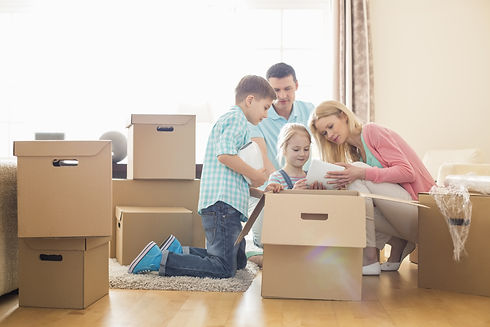 Family unpacking cardboard boxes at new