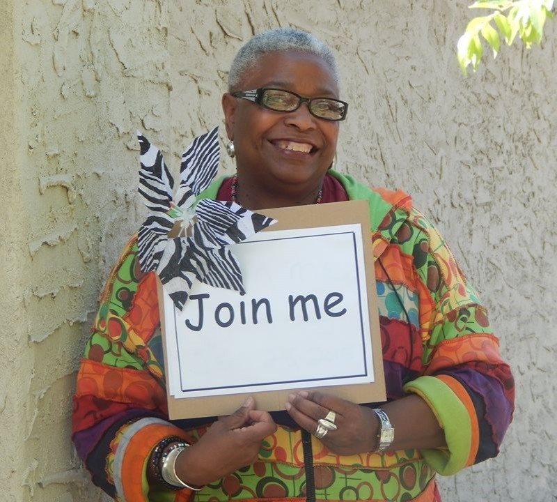 """Sacramento social justice advocate Faye Wilson Kennedy smiles as she holds a sign that reads """"join me."""""""