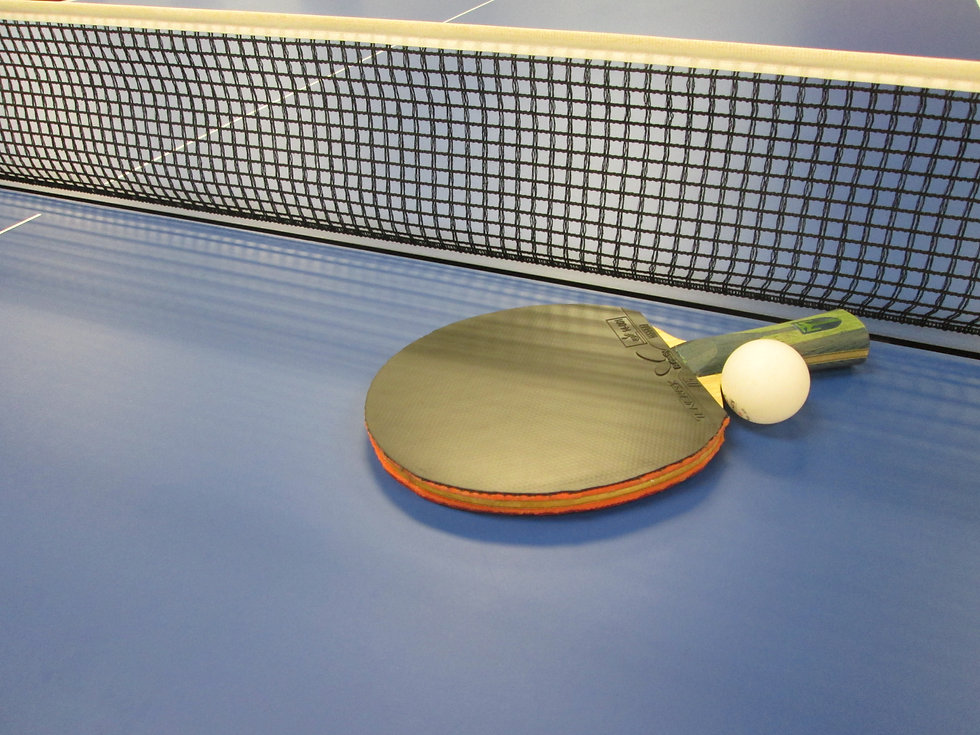 table tennis paddle with the white ball on a table tennis table