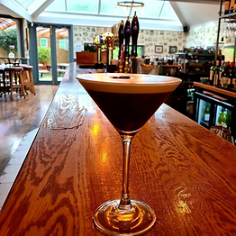 A photo of an espresso martini on the bar with blurred background of the beer garden.