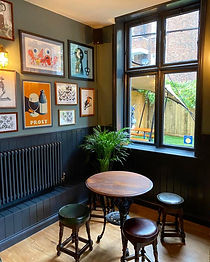 A photo of a cosy corner next to a window with lots of framed pictures on the wall.