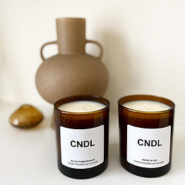 2 hand poured candles in front of a pottery jug
