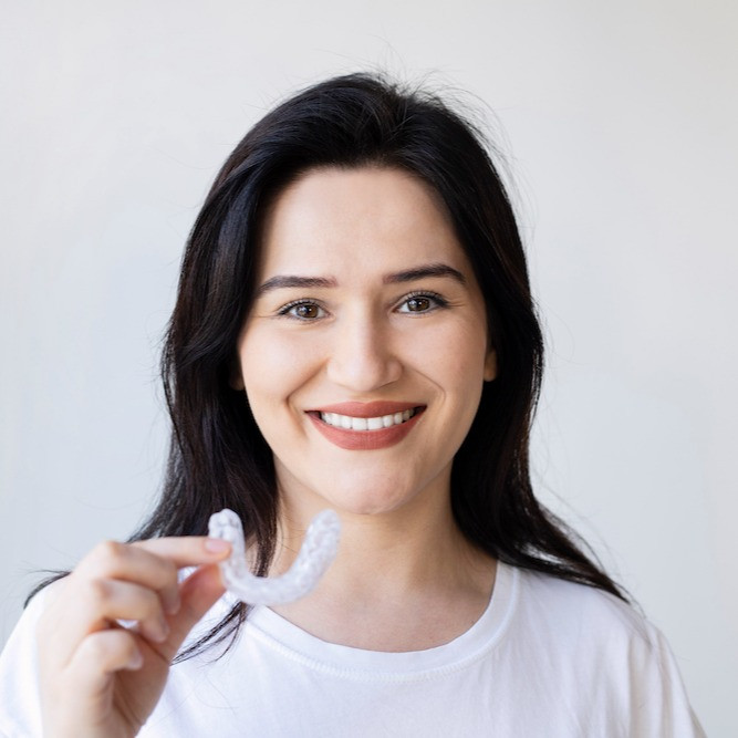 Invisalign, invisible braces held by a lovely lady who wants to straighter her crooked teeth