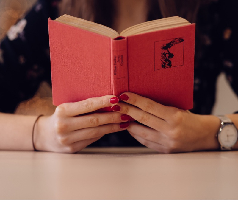 Woman's hands holding a red book
