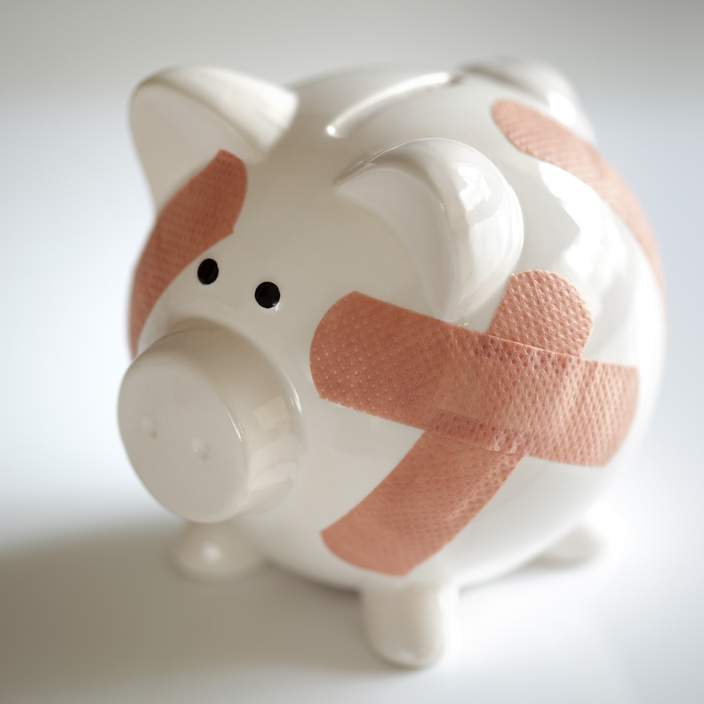 A white piggybank covered in pink bandaids sits against a gray background.