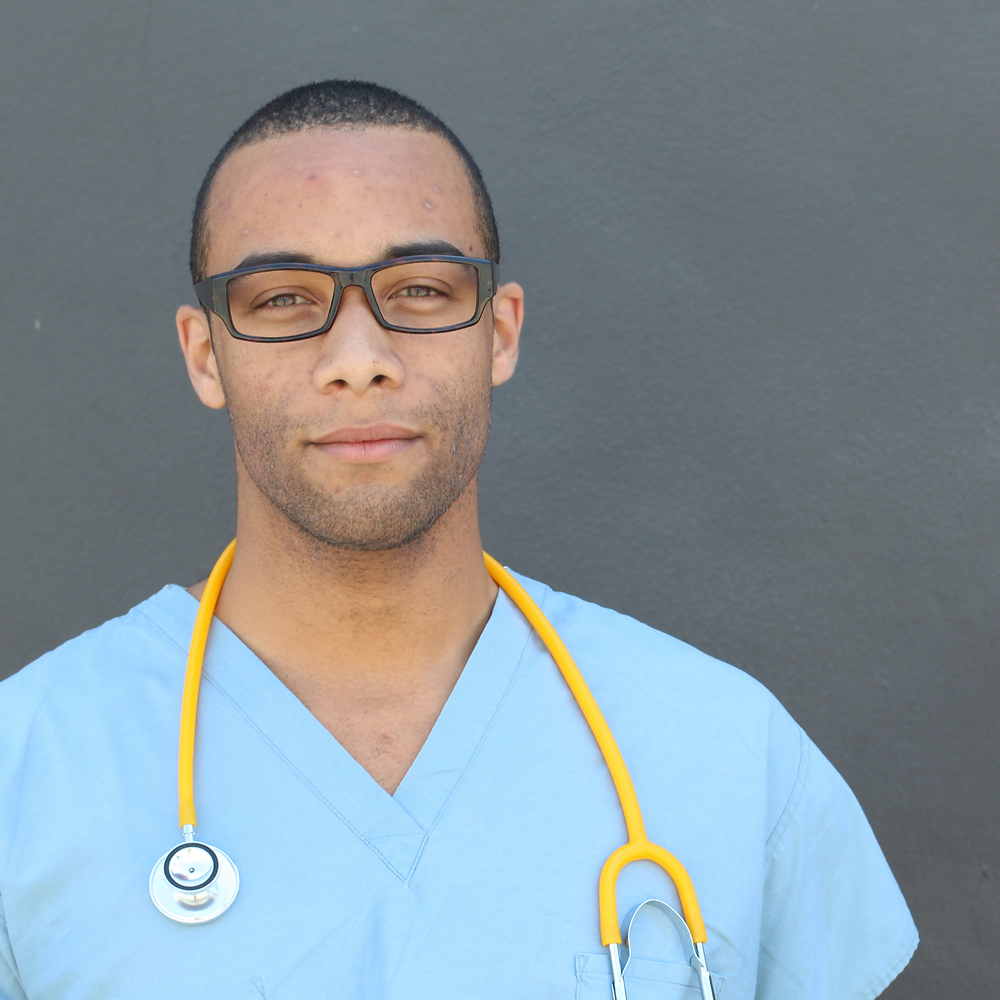 Black man with short hair and glasses wearing light blue scrubs and a yellow stethoscope around his neck.