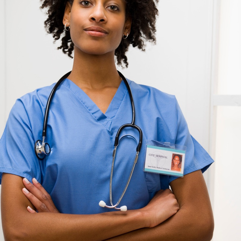 Nurse in blue scrubs wearing a stethoscope stands with her arms crossed.