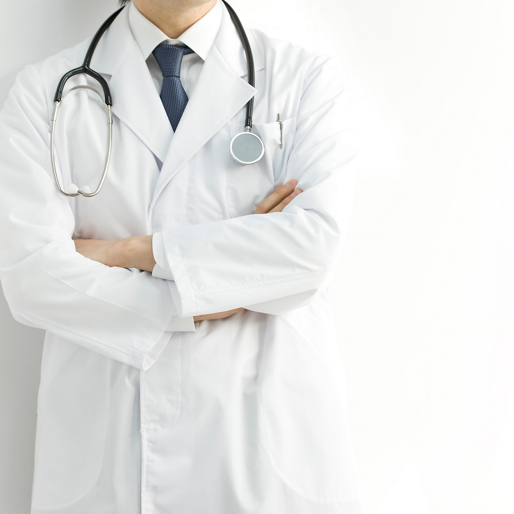 A white male physician in a tie and white coat stands with his arms crossed, wearing a stethoscope.