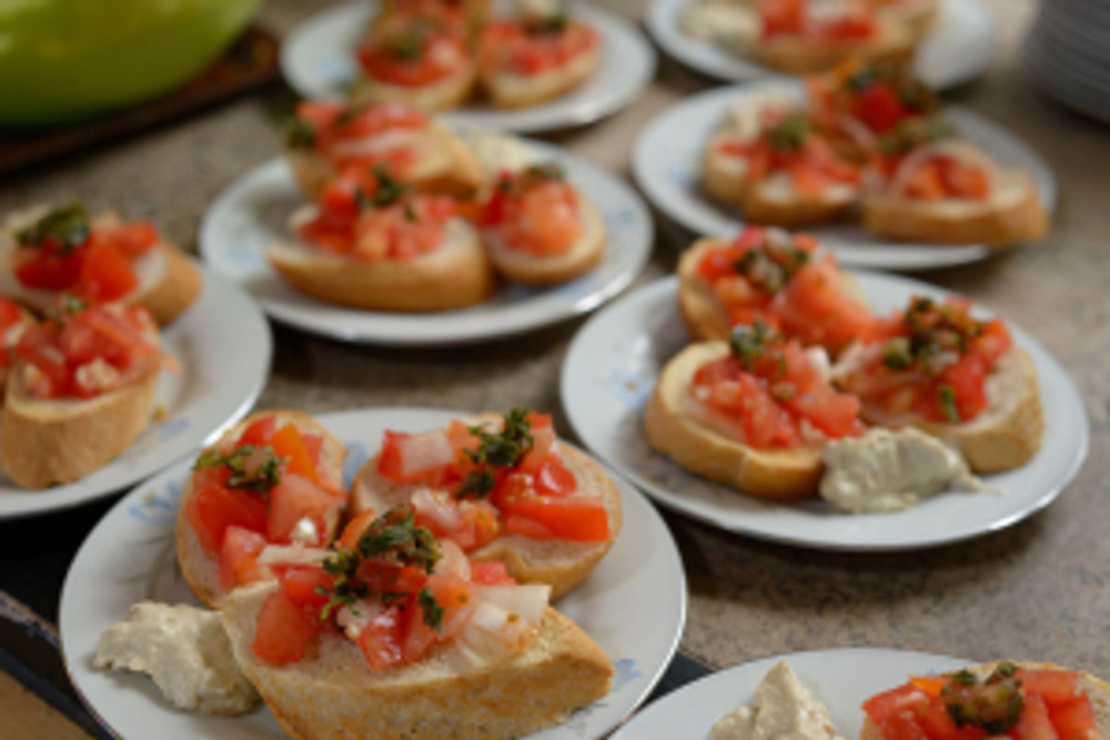 Saving surplus food from landfills. Free meals made by volunteers for the local community. Plates of bruschetta ready for serving.
