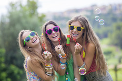 happy smiling group of teen girls blowing bubbles