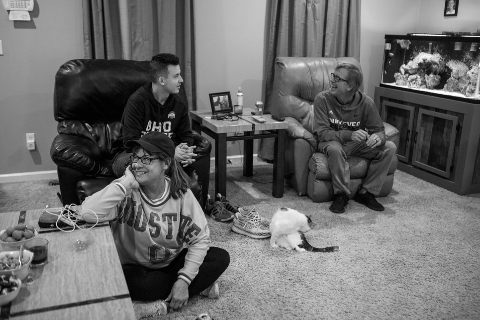 """Kremer watches a football game with her son and husband between the Ohio State Buckeyes and Wisconsin Badgers. """"I know we seem kind of crazy,"""" Kremer laughs, """"It's all about Ohio in this house. Since we're from Ohio, we watch all the football games. It's just something fun for us all to do together and especially for me when I'm not working or studying."""""""