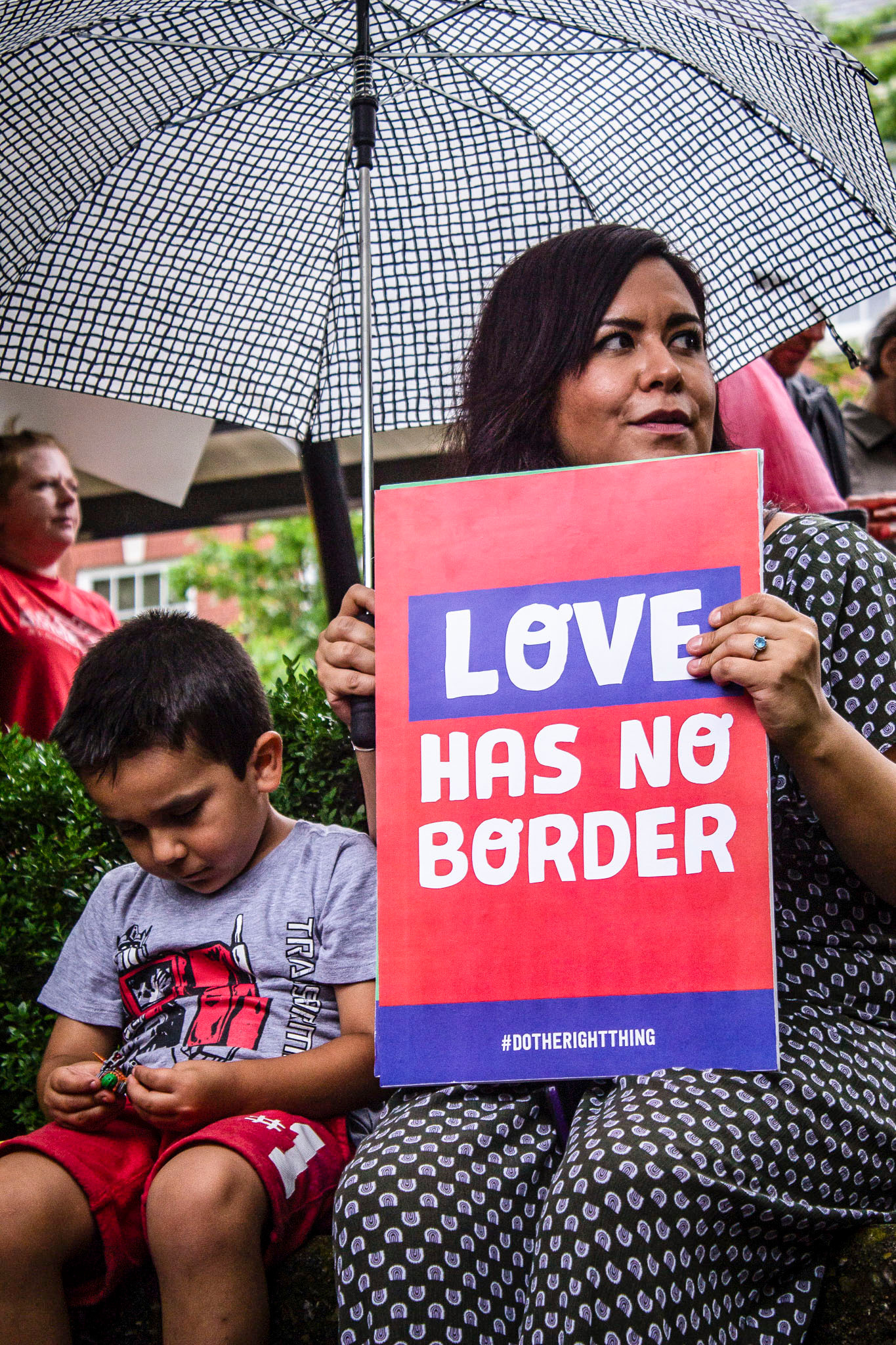 Lennon Loaeza (left) and his mother, Karla Pamanes (right)  listen to Claudia Caballero, the Executive Director at Centro Hispano, speak during a Families Belong Together rally outside of the Knoxville City County Building on Monday, June 25th, 2018 in protest of the Trump administration's zero-tolerance policy and the separation of migrant families crossing into the U.S. from their children.