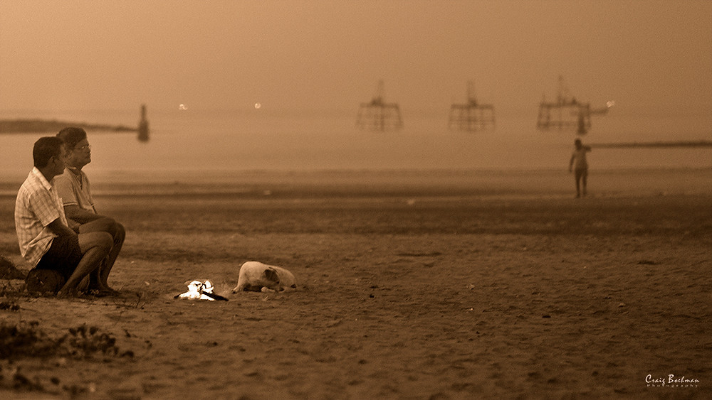 Two men with dog by campfire at Juhu Beach, Mumbai
